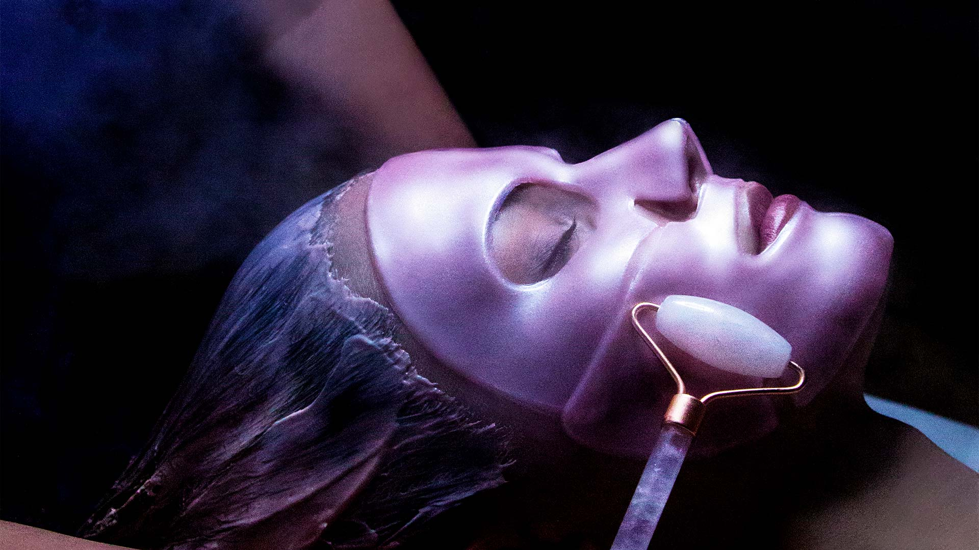 close up of a woman getting a spa treatment done. She has a pink mask on her face and a jade roller is moving across her face.