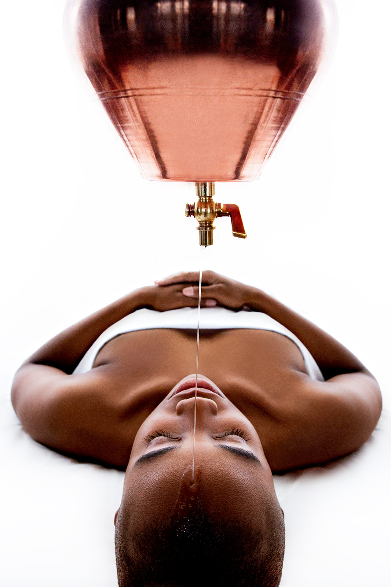 a woman getting a spa treatment where a liquid is dripped onto her head