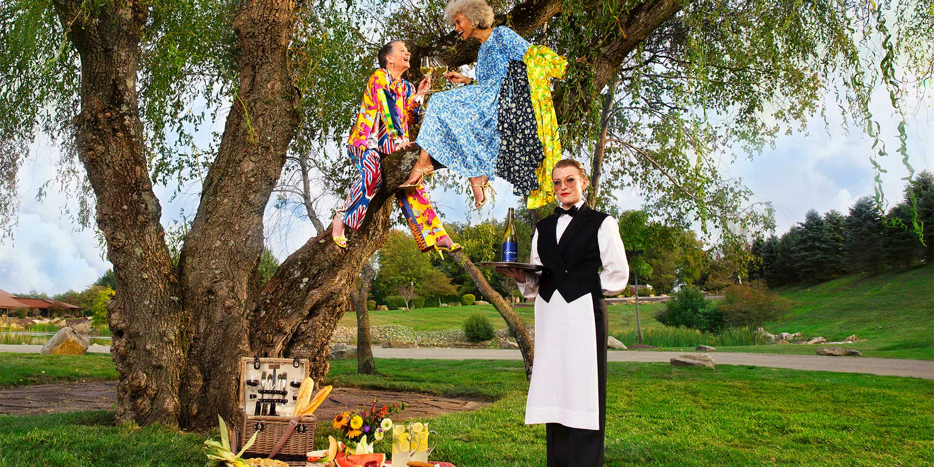 Two older women sit in a tree and enjoy a picnic on the ground catered to them by a woman standing in front of them with champagne in hand.