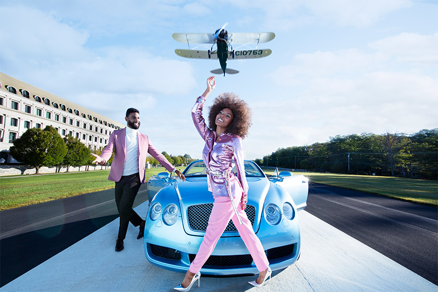 A woman wearing pink standing in front of a blue car with a man wearing pink next to the car and a plane flying above